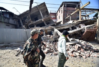 Security personel walk past a collapsed building following a 6.7 magnitude earthquake, in Imphal on December 4, 2015. At least eight people were killed and scores injured January 4, when a strong 6.7 magnitude earthquake struck northeast India, sending panicked residents fleeing into the streets even hundreds of kilometres away in Bangladesh. AFP PHOTO/ BIJU BORO / AFP / BIJU BORO
